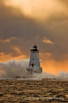 A strong wind and high seas had been battering the Lake Michigan coast all day long, and now storm clouds were moving in in force. The orange rays of the setting sun pierced the clouds and highlighted the turbulent scene around the Ludington, Michigan, north pierhead lighthouse.