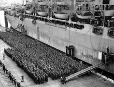 Hundreds of German prisoners wait (while US sailors and sailors watch from deck) to be loaded onto their transport ship in France—thei...