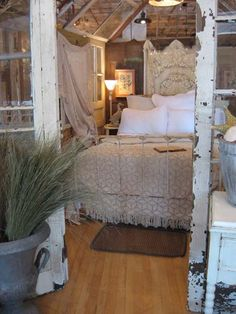 ..old windows used to create glass walls for this bedroom area...love the shabby chic worn white finish....