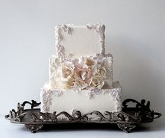 A cluster of off-white and light pink roses is framed by ornate decorations on this square wedding cake.