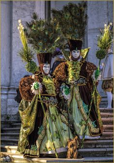 Greens and browns and peacock feathers on these costumes almost make the cutest little dog invisible at the Carnival of Venice 2016