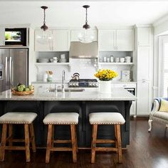 black island with white upper cabinets, wood stools, school house lights, kitchen display shelves