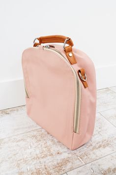 Pink Leather Backpack    Detachable + Adjustable Straps    Silver Zipper, Clasps, + Details    Exterior + Interior Pockets    Backpack + Purse Option    Also Available in Navy, Toffee, + Champagne