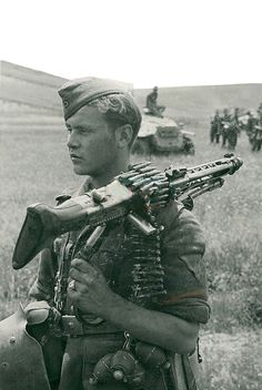 A young wehrmacht soldier carrying an MG42 machine gun with bipod.