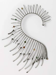 "The circa 1964 ""Boa†necklace is also suggestive of a sea horse. The spikes emanating from the curved spine are decorated with eight bezel-set hard stones."