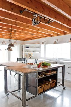 I love this steel-framed island on castors, with open shelving. Perfect for an industrial-style kitchen, and very practical. The lighting fixture in the foreground is an antique ship searchlight.