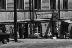 Hertankatu 13. Puutalo, jonka kivijalassa Jalkinekorjaamo - Skoreparation. Ovella romaninainen. Vasemmalla verkkopaitainen mies tuo lautoja viereisestä ovesta. 1970