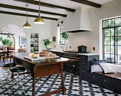 Love this Spanish style kitchen by Jessica Helgerson Interior Design. The amazing floor tiles, black cabinetry, brass pendant lights, gorgeous wood pieces. Project Manager: Em Shephard. Photos by Lincoln Barbour for Jessica Helgerson