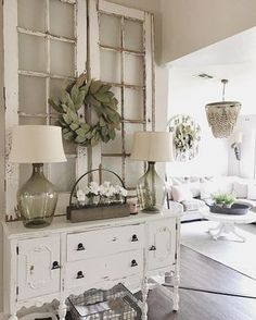 Fresh white farmhouse style dresser with magnolia wreath and antique windows