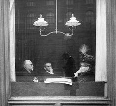 Blick in ein Kaffeehaus in der Babenbergerstraße (Nr. 145) gegenüber dem Kunsthistorischen Museum. Im Fensterglas spiegelt sich nicht nur dieses, sondern auch Dr. Emil Mayer, wodurch man deutlich seine Technik der unbemerkten Aufnahme vor Augen geführt bekommt. Wien, ca. 1910.