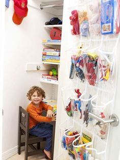 Clever Closet - The small closet does big work: The left side has shelves and bars for Julian's clothes, and on the right is a built-in art desk topped with shelves for his books, games, and puzzles. A clear shoe organizer inside the door holds his action figures and trinkets. Discover more kids room organizing tips and ideas @ http://kidsroomdecorating.net