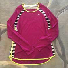 Nike drifit long sleeve top size M Gently loved Nike DRI-FIT long sleeved top. Pink with hot yellow piping; white and black striped pattern adds fun detail to short. Perfect to layer for upcoming chiller weather. All purchases from my closet come with free travel sized Bliss products. Nike Tops