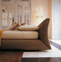 Letto Exige LA FALEGNAMI. Un design affascinante per il movimento sinuoso della sua testata. Il basamento si adagia con forma leggermente allargata verso il pavimento. Tessuti e pellami prestigiosi, per chi vuole rifuggire da tutto ciò che è banale e massificato. Double Beds, Ferrari, Lounge, Couch, Design, Furniture, Home Decor, Shape, Houses