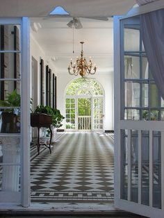 outdoor indoor verdandah patio sunroom design with chandelier, black white checkerboard tiles white windows french doors