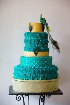 Stunning turquoise and gold peacock wedding cake with gold cake stand. | Kansas City Wedding Cakes |