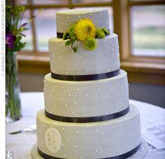 An elegant yellow, gray, and white wedding cake.