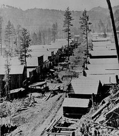 A photograph of Deadwood in 1876. General view of the Dakota Territory gold rush town from a hillside above.