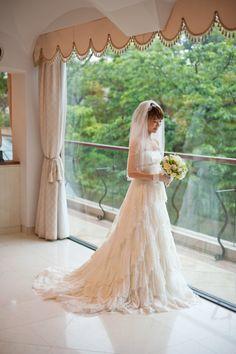 QED CLUB(キューイーディークラブ)にてご結婚式をされた花嫁様。 レースを幾重にも重ねたナチュラルテイストのエンパイアのウェディングドレスに ビジューのリボンカチューシャとビジューイヤリング、ミディアム丈のベール。 ゆるふわアップのヘアスタイルにブライダルアクセサリーを ナチュラルでスタイリッシュにコーディネート。 緑あふれるガーデンウェディングに映える花嫁コーデですね。