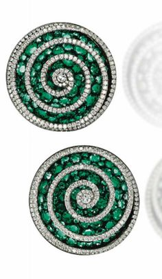 A Pair of Emerald and Diamond 'Spiral' Ear Clips, by JAR – Each modelled as a three-dimensional diamond-set spiral thread overlying a concave pavé-set emerald disc, mounted in platinum, gold and silver, 2002, 3.0 cm, in pink leather JAR case Signed JAR