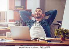 Satisfied with work done. Happy young man working on laptop while sitting at his working place in office