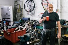 Portrait of senior adult bicycle mechanic holding coffee cup in workshop.
