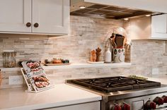 Natural Stone Small Kitchen Backsplash With White Wooden Cabinets Also Wooden Shelf And White Glossy Countertop Also Kitchen Appliance Stove And Undercabinets Lamp, Beautiful Kitchen Design with Small Tile, Mosaic Backsplash Ideas