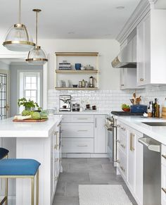 Well appointed white and gray kitchen is lit by prismatic light pendants hung above a light gray island seating backless blue counter stools.