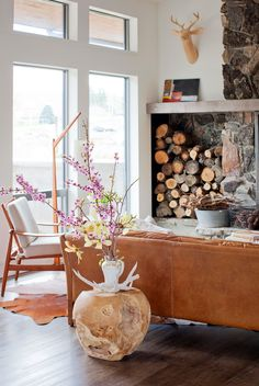 A rustic living room with warm woods, cognac leather and a touch of fuchsia. Photo by Janis Nicolay.