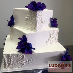 Bavarian Cream Cheesecake wedding cake. Offset square stacked 3 tier featuring flora swirls and purple flowers