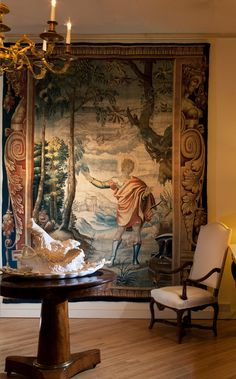 Hanging behind a large gilt bronze chandelier a late 17th century Mortlake tapestry of Apollo fills the wall, Julia Boston Antiques, UK