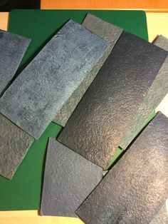 Painting egg carton box material to imitate slate, for slate roof tiles. Mix black, white, blues and even greens and browns to get a natural effect.