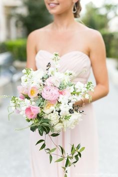 springtime maid of honor bouquet of light pink peony, white o'hara garden rose, white majolik spray rose, white clematis, light pink parrot tulip, white stock, small succulent, spirea, jasmine trails & greenery