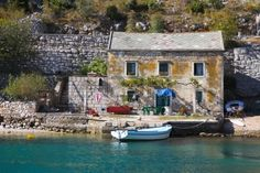 View of old stone house with a wooden boat moored in a little croatian bay