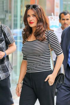 Salma Hayek steps out in a classic summer look with horizontal stripes, black loose pants and a red lip