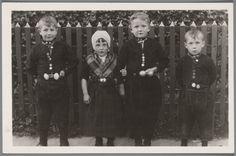 Twee jongens en een meisje poseren voor een hekje. De kinderen zijn gekleed op z'n 'Zondaags', de jongens compleet met (volwassen) goud en zilver en Urker broeksknopen. 1920-1929 #Urk