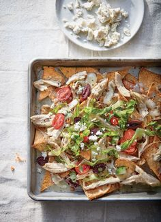 Dinner doesn't get much easier, or more fun, than sheet pan nachos. Toast the chips in 2 batches first; then combine the chips, pile high with toppings, and return to the oven to heat everything through. The dish takes a detour to Greece with pita chips, a shredded Greek salad, and crumbled feta.