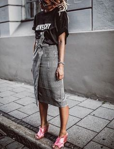 a plaid skirt styled with a black graphic tee and pink mules