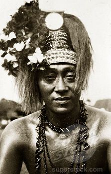 Samoan chief in 'meke' dress. Portrait of a Samoan chief wearing traditional 'meke' dress. His long hair is worn up, decorated with a beaded headdress and flowers, and his neck is adorned with long strings of beads. Suva, Fiji, 21-27 May 1924. Suva, Viti Levu, Fiji, Pacific Ocean, Oceania
