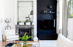 hide the TV on a painted black wall or bookshelf (via Apartment Therapy)
