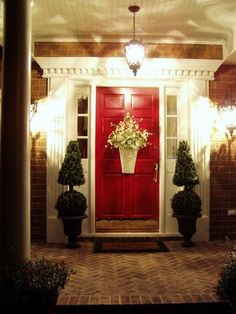 "Red front door with lit porch and topiary screams ""welcome"" and curb appeal."