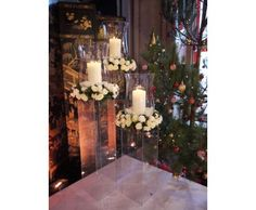 White rose wreaths and candle lanterns on perspex plinths at Christmas