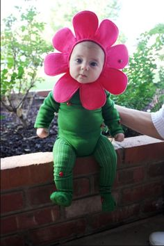 "Flower: For the sweetest costume out there, dress your baby in green and add a bright pink flower crown. Add some ladybugs up her ""stems"" and watch the little one bloom. Find more easy DIY Halloween costumes ideas for kids and babies that are cute, spooky and funny here."