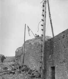 """Flying from a splayed barrel of a Nazi ack-ack gun atop the citadel in St. Malo, France, """"Old Glory"""" indicates the victory which American troops won after four days of concentrated assault on the city. Photo dated August 17, 1944, one day after the Germans surrendered. From the Webmaster's collection."""