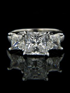 The Happy holds any center stone shape in a prong setting atop a smooth edge shank, accented with Princess cut side stones in 4 prong basket settings. Best Engagement Rings, Three Stone Engagement Rings, Three Stone Rings, Princess Cut Rings, Princess Cut Diamonds, Man Made Diamonds, Wedding Rings For Women, Wedding Sets, Love Ring
