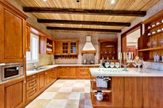 Large kitchen with peninsula designed with wood cabinets.  Floor is pink and off-white checkered tiles. Design improved with wood ceiling supported by dark wood beams