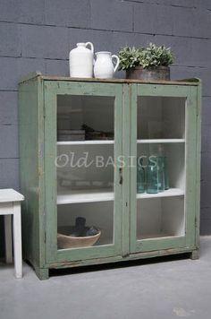 Vitrinekast 10007 - Brocante houten vitrinekast met een oud groene kleur. De kast heeft een mooie geleefde uitstraling, bovenop de kast zit een opstaande rand. Achter de deuren is het meubel wit en zitten twee vaste legplanken.