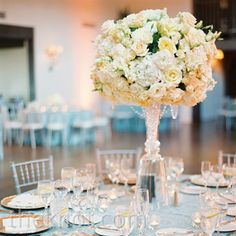 Tall glass trumpet vases overflowing with floral arrangements topped vibrant blue linens.