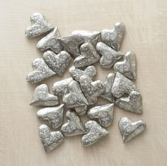 Hewn of lead-free pewter, weighty tokens of affection await discovery tucked in a pocket or under a pillow. Made in USA. Set of 25.