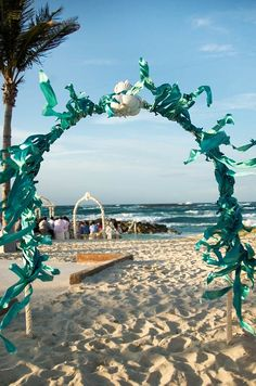 Guests enter through a sea blue colored archway for the wedding ceremony on the beach.