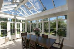 A crisp and fresh looking #conservatory, used as a #dining room and #designed to maximise the views of the L shaped #garden.